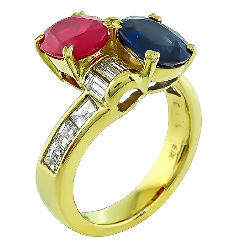 This elegant 18k yellow gold ring is set with lovely oval cut ruby and sapphire that weighs 1.85ct and 1.71ct respectively. The sapphire and ruby are accentuated by sparkling baguette and carre cut diamonds that weigh 1.10ct. graded G-H color with