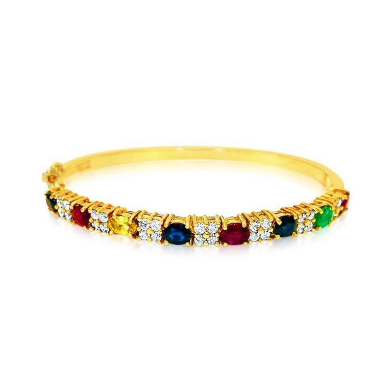 18k yellow gold.   Precious gemstones: ruby, blue sapphire, yellow sapphire and emerald.  100% natural earth mined gemstones. Carat weight of each gemstone: 0.75ct.  Cut: Oval cut gemstones set in prongs.  Diamonds: 0.80ct total. Round brilliant cut