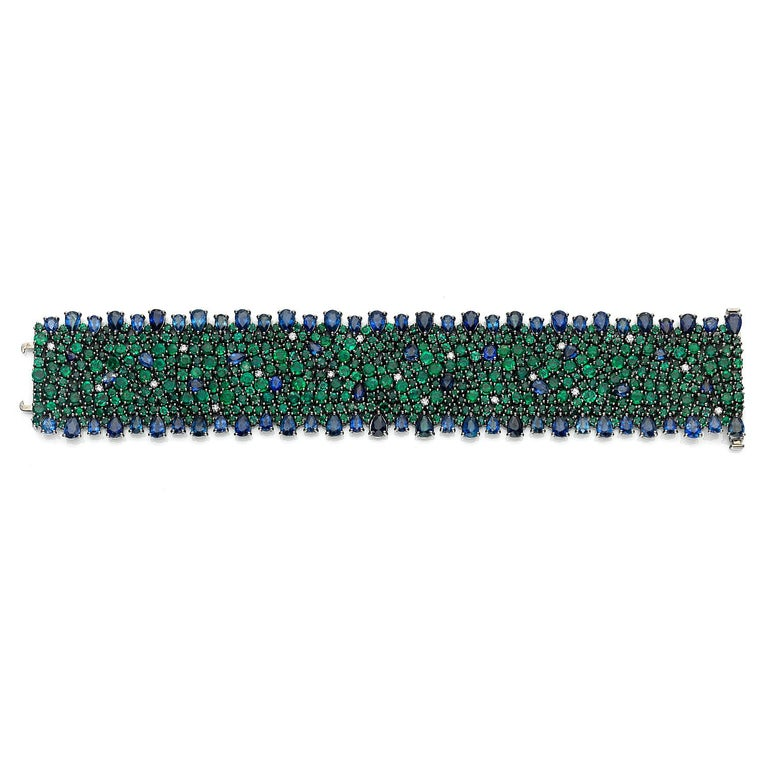 Earthly Hues Collection   Blue Sapphire, Emerald and Diamond statement bracelet set in 18K black rhodium gold.   Sapphire: 27.43ct total weight. Emerald: 29.45ct total weight. Diamonds: 0.57ct total weight. All diamonds are G-H/SI stones.