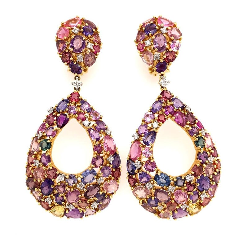 Play Of Colors Collection   Multi color yellow, pink, purple, green and blue Sapphire chandelier earrings set in 18K yellow gold.   Multi Sapphires: 32.29ct total weight. Diamonds: 0.82ct total weight. All diamonds are G-H/SI stones.