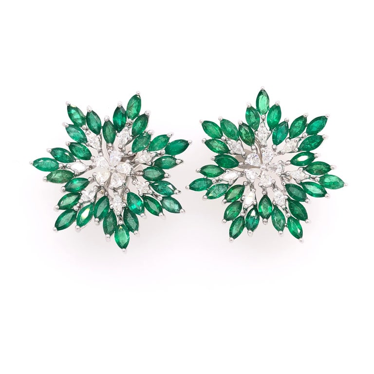 Green Lagoon Collection   Emerald and Diamond flower shaped stud earrings with a clip post set in 18K white gold.   Emerald: 7.47ct total weight. Diamonds: 1.08ct total weight. All diamonds are G-H/SI stones. Diameter - is approximately