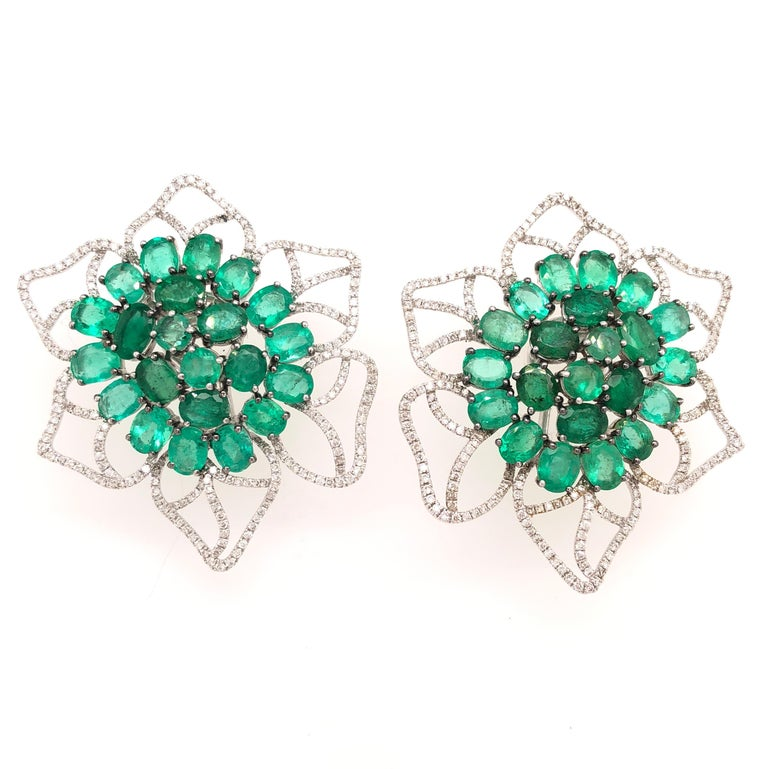 Green Lagoon Collection  Large Emerald and Diamond flower stud earrings set in 18K black rhodium gold and white gold. The center Emeralds are set in a gradient style from darker in the center to lighter tones on the edges.   Emerald: 15.58ct total
