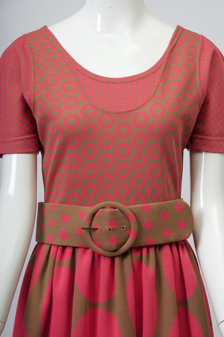 A great find, this Rudi Gernreich c.1970s dress is fashioned of polyester knit featuring a dot design in varying sizes in pink and olive, the bodice simulating a jumper and tee shirt form with scoop neck and short sleeves, each of contrasting small