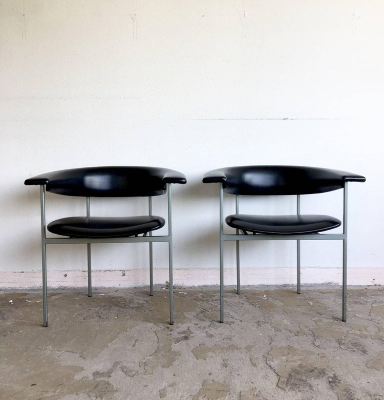 This pair of Dutch Minimalist armchairs were designed by Rudolf Wolf for Gaasbeek-Van Tiel in the early 1960s. The chairs come from the Meander series and feature a grey metal base with Black faux leather upholstery. The Gamma Club chair was named,