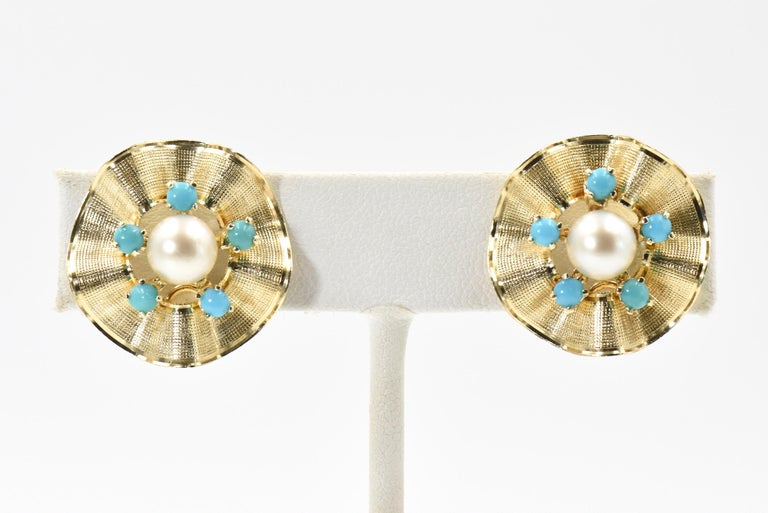 Classic elegant three dimensional flower earrings featuring a centrally set 6.8 mm cultured pearl set between 5 prong set turquoise beads.  The outer gold frame is rubbled and has a textured finish with a shiny edge.  The earrings are 14k yellow