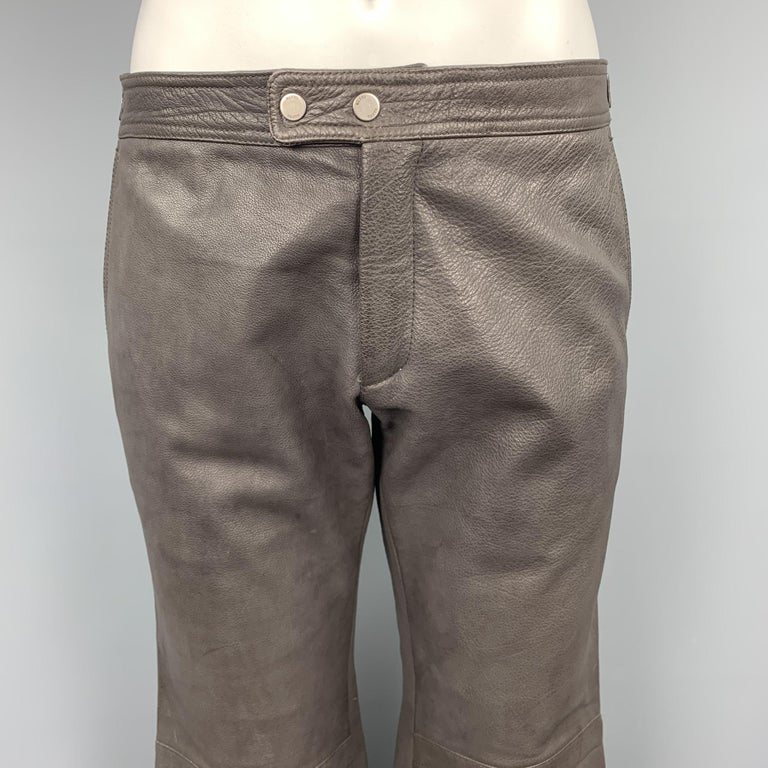 RUFFO biker pants comes in textured taupe leather with quilted knee pads, snap tab waistband, and zip cuff legs. Made in Italy.  Very Good Pre-Owned Condition. Marked: (no size)  Measurements:  Waist: 17 in. Rise: 9.5 in. Inseam: 36 in.