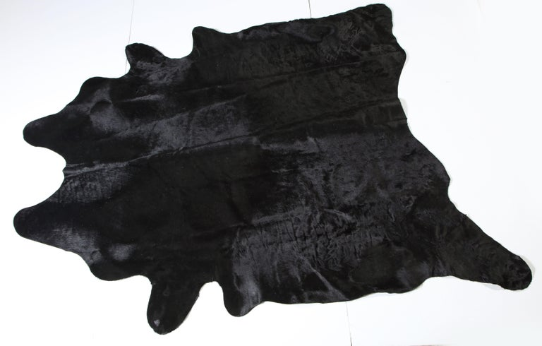 Cow hide, black. Lightly used.  If you measure from each leg, one direction is 110 inches and the other direction is 109 inches.