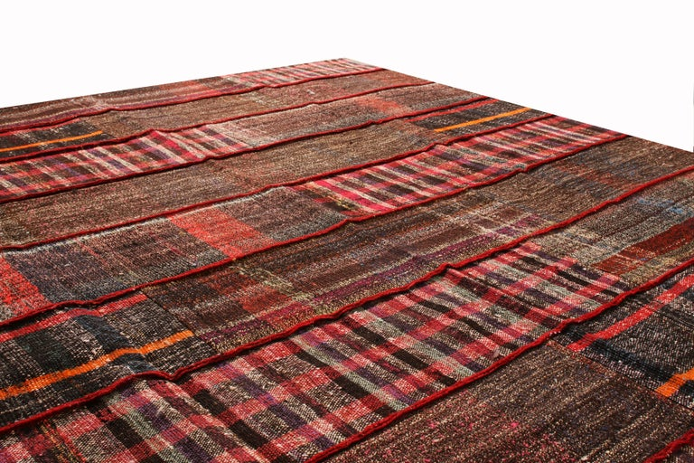 Originating from Turkey, Rug & Kilim's contemporary wool Kilim rug is inspired from a distinct family of traditional families, woven with a mixture of patchwork aesthetic and column-based pattern. Bright and rich arrays of red, with notes of purple,