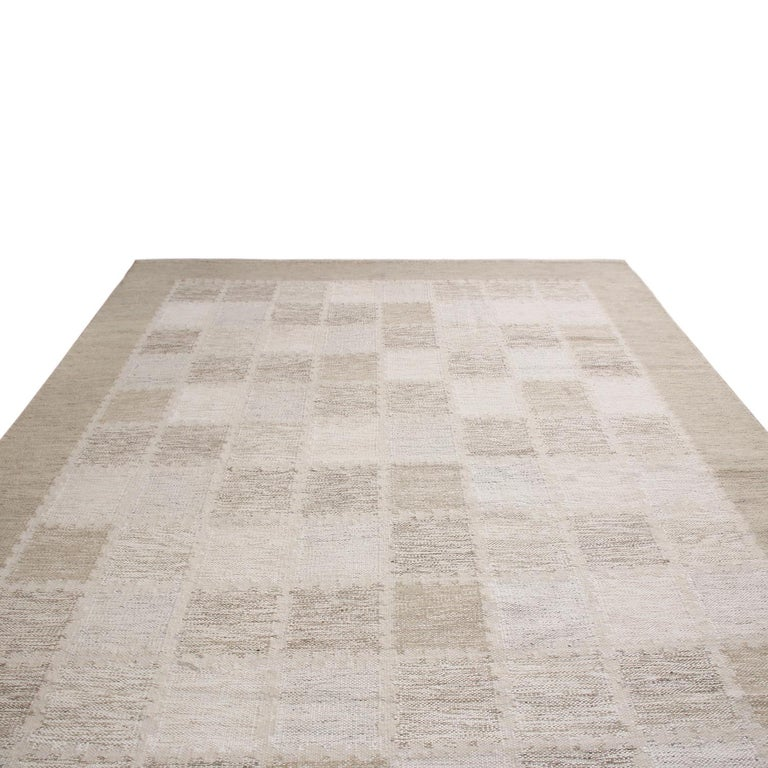 Originating from India, this hand knotted wool pile rug hails from Rug & Kilim's Scandinavian-inspired collection, featuring a distinct tribal geometric all-over field design with off-white, gray, and multi-tonal beige brown colorways bound in