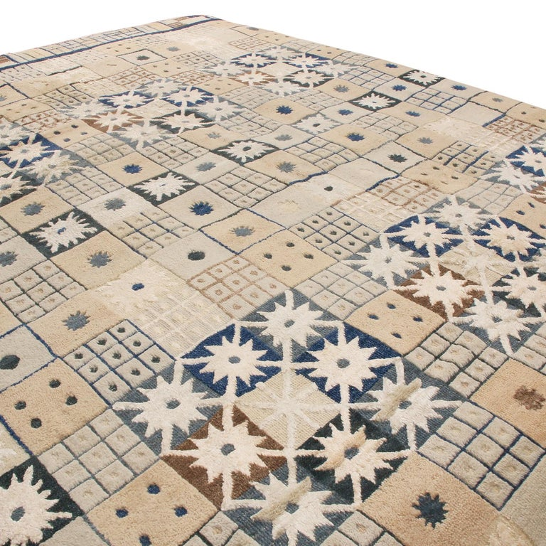 Originating from India, this hand knotted contemporary pile rug hails from Rug & Kilim's Scandinavian-inspired collection, featuring a distinct patchwork all-over field design with cream and multi-tonal beige-brown colorways with vibrant blue