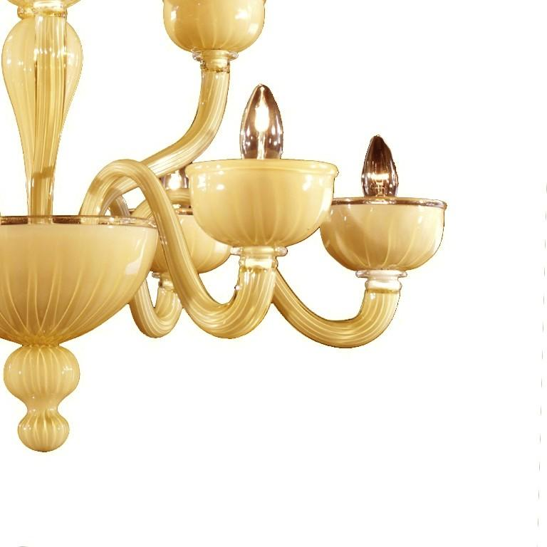 This elegant chandelier is entirely handcrafted of Venetian glass by Murano master glassmakers. The central structure features a two-tier design with six curved arms and three, smaller arms on top all ending with large bobeche. The delicate amber