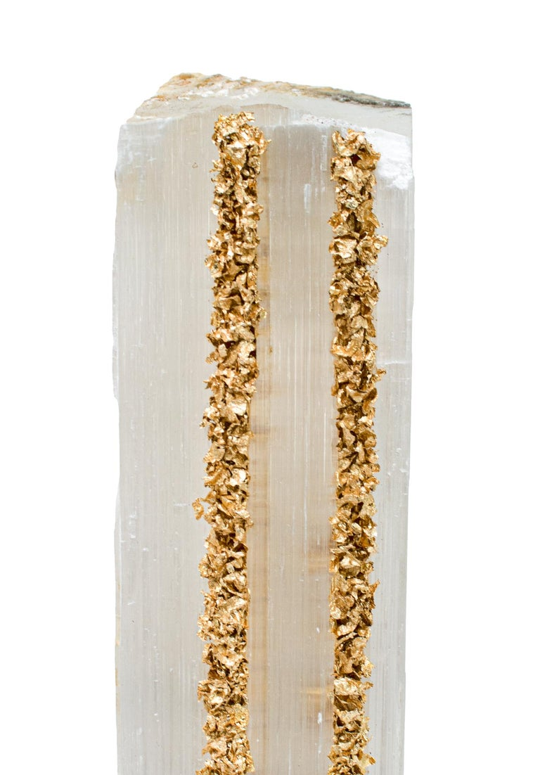 Ruler Selenite with gold leaf on a Lucite base. Selenite logs are single, prismatic selenite crystals from Morocco that were formed in extensive beds by the evaporation of ocean brine. This mineral is characterized by a silky, pearly luster called