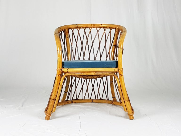 This beautiful armchair was produced in Italy between the 1960s and the 1970s. It is handmade from rush and rattan and remains in pretty good condition: slight leaks of protective varnish on the back; the pillow was covered with blue velvet.