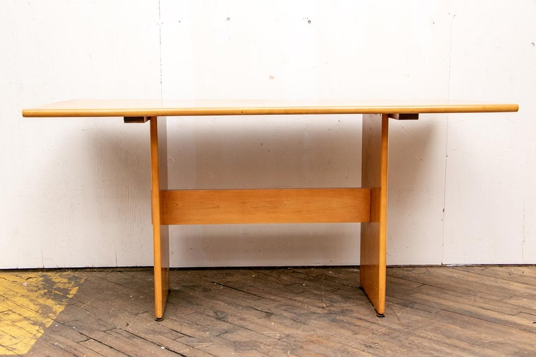 Sticker on the table. Blond maple rectangular table with rounded top ends, a flat stretcher and flat side supports. Along with two matching benches of the same construction.