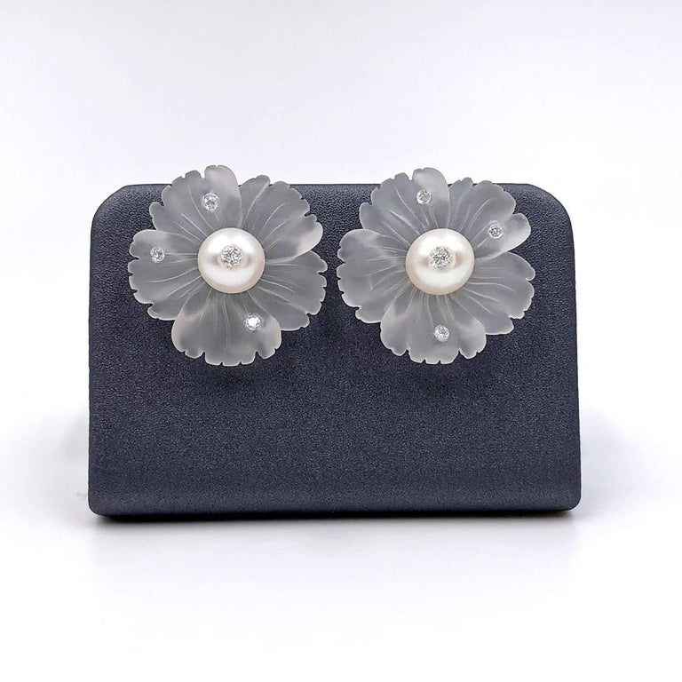 Flower Stud Earrings handmade by jewelry artist Russell Trusso featuring a matched pair of hand-carved rock crystal flowers with freshwater pearl centers, each accented by the artist's signature embedded round brilliant-cut white diamonds (total