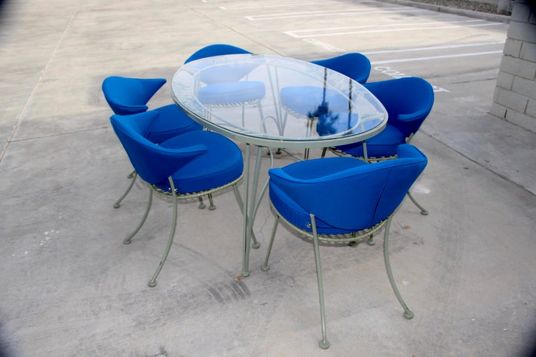 A somewhat rare group of 6 Russell Woodard Klismos type chairs re-done in a royal blue sunbrella fabric and a pinecrest pattern table. The back cushion is attached the seat cushion is removable. The table dimensions are 70.5 inches long, 41 inches