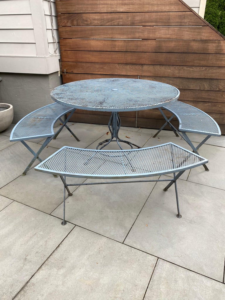 Nice Russell Woodard iron table and 3 curved benches. Set has a slightly worn blue gray paint finish. Table is 47'5 round and 29