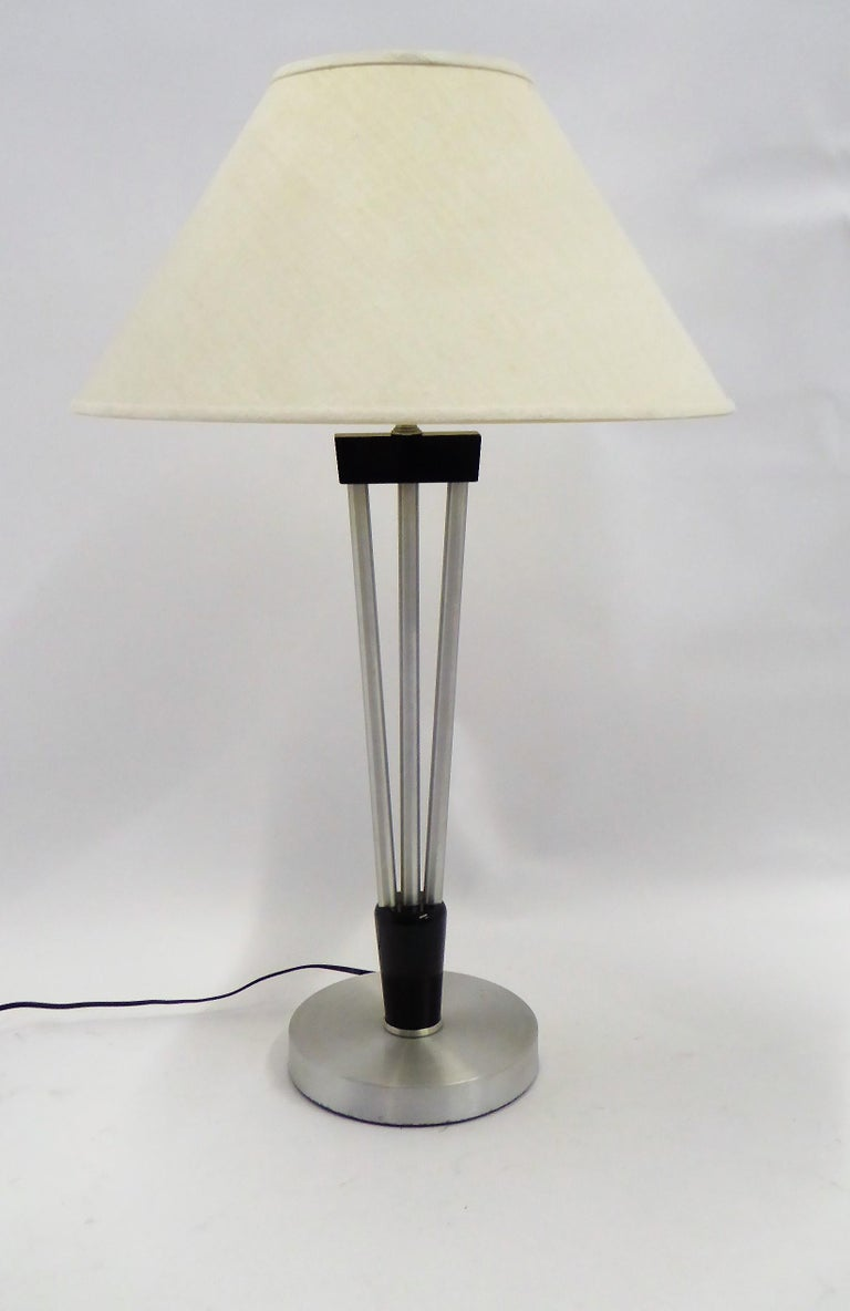 Wonderful late 1940s table lamp by Russel Wright. The socle base of circular spun aluminum topped by an ebonized carved wood base to three up climbing aluminum poles to an ebonized wood shoulder continuing to a neck socket holding the milk glass