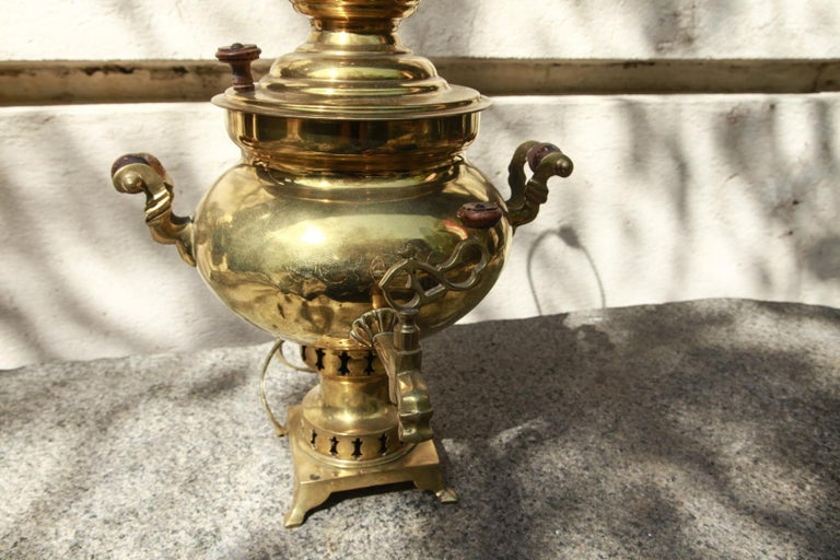 Late 19th century Russian samovar that has been converted to a lamp and fitted with a black hardback shade. The samovar is typical in form with a bulbous two handled body resting on a small four footed base. It has been recently wired and is fitted