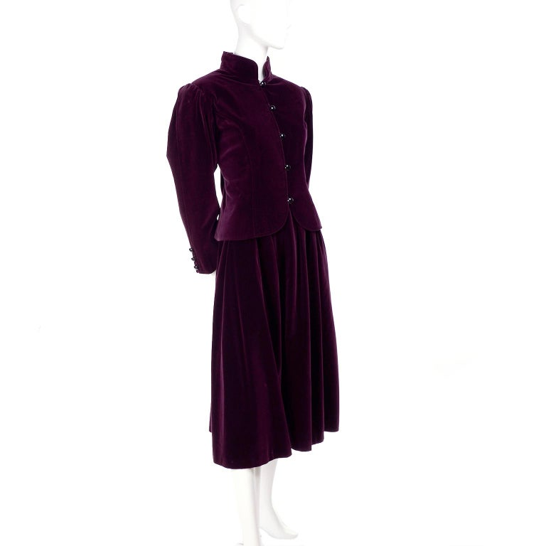 This sensational vintage wine or burgundy velvet skirt and jacket ensemble from Yves Saint Laurent is so lovely.  The suit includes a Mandarin collar jacket and a softly pleated skirt.  The jacket has YSL''s classic round buttons up the front and on