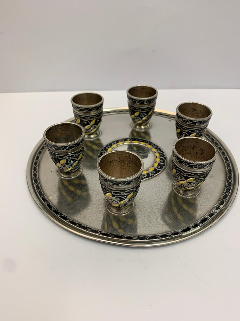 A Russian silver and enamel drinking set, including 6 small drinking/shot tumblers and large silver ewer. All intricately decorated upon a circular silver tray.