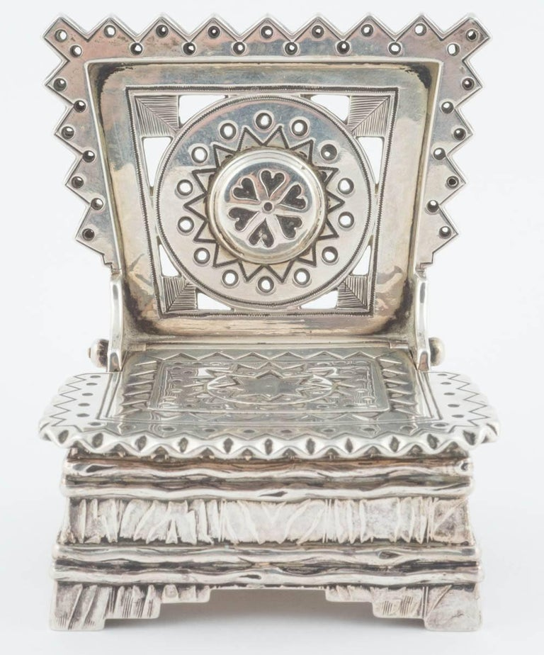 From the Romanov era of typical form, the silver simulating a traditional wooden salt chair, bark, the hinged lid and pierced back decorated with star, heart and zigzag motifs recalling Old Russian designs, the base of trompe l'oeil texture, a
