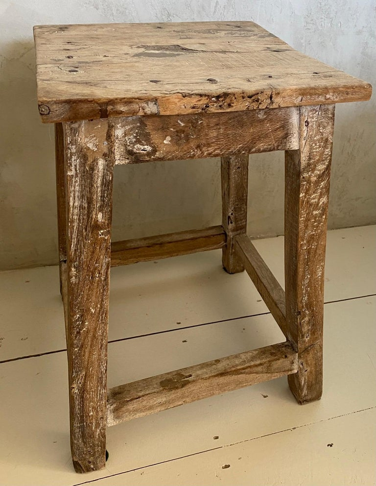 The antique Asian stool has a square top and a balanced form with timeless rustic appeal. Beautifully worn from a century of use, the aged wood patina adds rich texture to the home. It can be used for side table, end table, or extra seating. Great