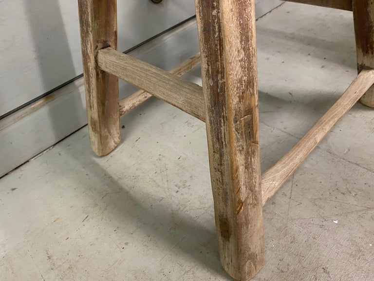 The rustic Chinese stool from the Qing Dynasty period with mortise-and-Tenon joinery techniques with pegged legs that fit into the seats and stretchers that fit into the legs for sturdy construction. The stool has a balanced form and timeless rustic