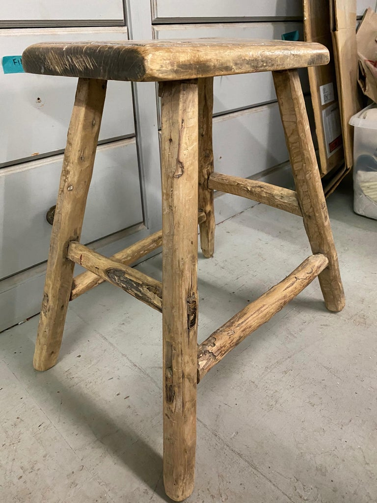 The rustic Chinese stool from the Qing dynasty period with mortise-and-tenon joinery techniques with pegged legs that fit into the seats and stretchers that fit into the legs for sturdy construction. The stool have a balanced form and timeless