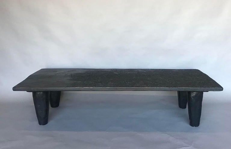 Rustic modern coffee table with a 19th century top and newly made conical shaped legs. The top has old termite damage which has given it a very interesting patina! no live bugs, we have everything fumigated. There are two birds carved into the wood.