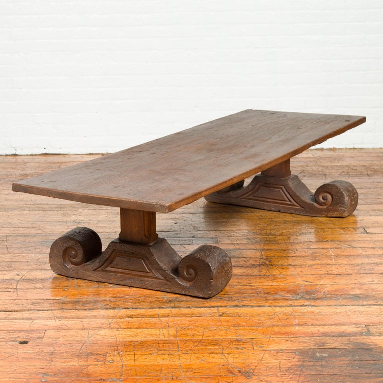 An antique Chinese elmwood coffee table from the 19th century, with scrolling base. Born in China during the 19th century, this rustic yet elegant coffee table features a rectangular top sitting above a base that catches our attention with its large