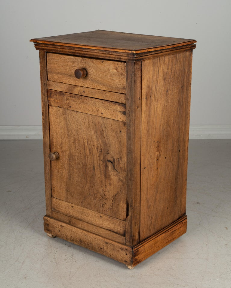 A rustic Country French side table or nightstand made of thick planks of solid walnut with faded distressed finish. Small dovetailed drawer above a cabinet door opening to one shelf. Large turned wood knobs. Please refer to photos for more details.