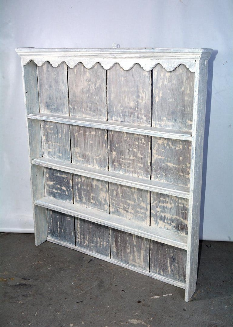 Rustic French country Provincial style wood hutch with 3 shelves. Each shelf has a rail on the shelf for displaying plates or platters. Shelving unit has been white washed. Scallop details adds further charm.