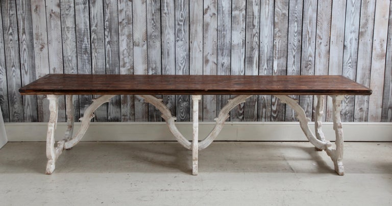 A beautifully hand crafted rustic farm house table from Tuscany, Italy finished in a two tone patina of gesso white with a contrasting natural wood finish for the top. This particular piece is rare because the joints between the legs of the table