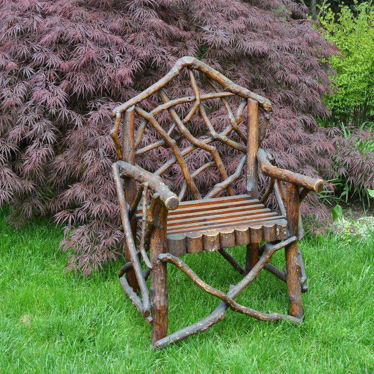 A rustic wooden twig armchair, the pointed crestrail above an interlaced splat of open twigwork over outscrolled arms above a slatted rectangular seat with scalloped apron raised on rounded twig supports joined by X-form stretchers, English, circa