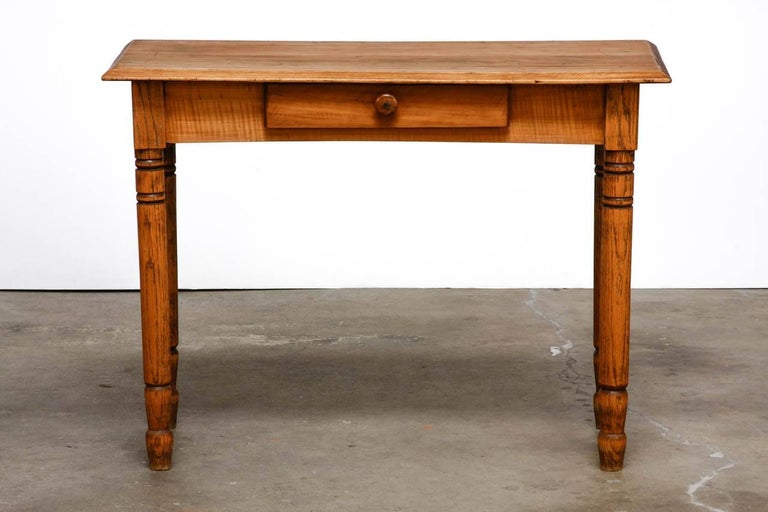 Rustic farmhouse oak work table or console fronted by a single drawer. The work surface has a beveled edge and the case is supported by round turned legs. Each leg is decorated with rings and spade style peg feet. This table could also serve as a