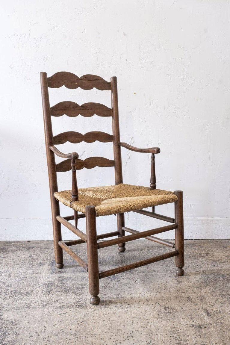 Rustic French ladder back armchair, circa 1840-1860. The shape of the scrolled ladder back slats and delicately carved arms of this chair are characteristic of furniture from the Southwest region of France. The rush seat has a beautiful patina and