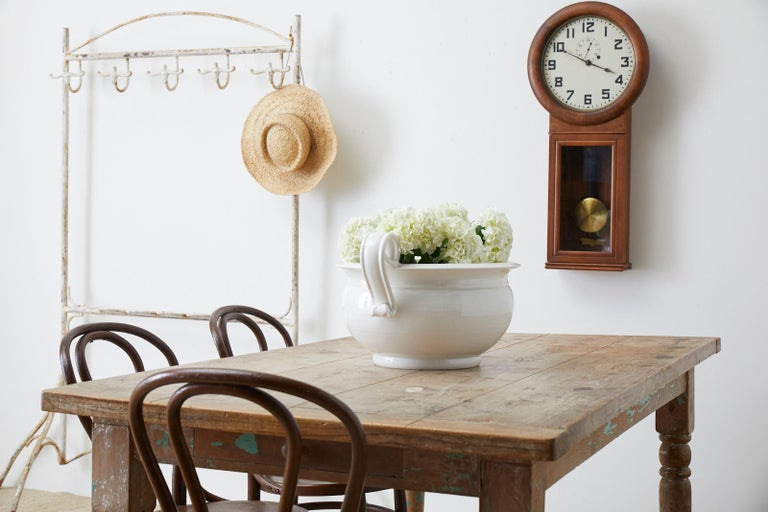 Rustic French country farmhouse work table or dining table constructed from pine. Features a well-worn faded patina on the wood with old lacquer paint remnants of teal green paint. Supported by thick turned legs with a storage drawer on each end.