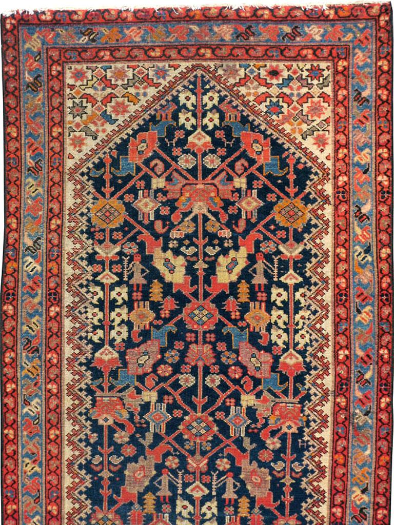 An antique Persian Malayer rug in runner format handmade in the early 20th century with a navy background and secondary tones in rust red, ivory, and light blue.  Measures: 3' 6
