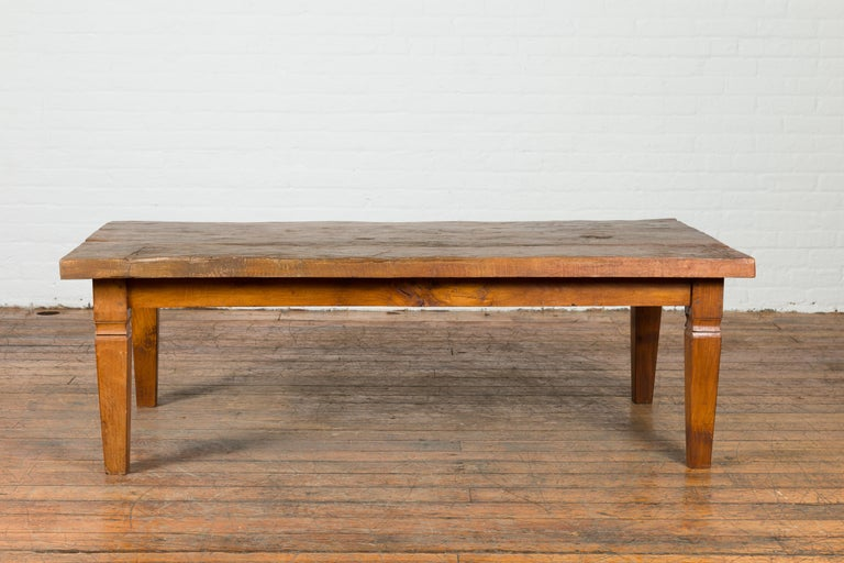 A rustic Indonesian antique wooden coffee table from the 19th century, made from a slab of wood. Created in Indonesia during the 19th century, this coffee table draws our attention with its rustic planked top with nicely weathered appearance,