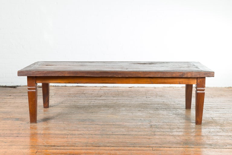 A rustic Indonesian wooden coffee table from the 19th century, with tapered legs. Created in Indonesia during the 19th century, this coffee table draws our attention with its rustic planked top boasting a nicely weathered appearance, sitting above