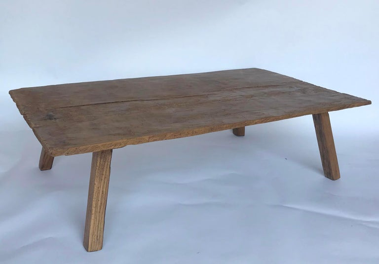 Coffee table made with an antique, very rustic one wide board top from Guatemala. Newer legs have been finished to match the top. Table is hand hewn but flat to place things like glasses and accessories. There are old worm holes in the top showing