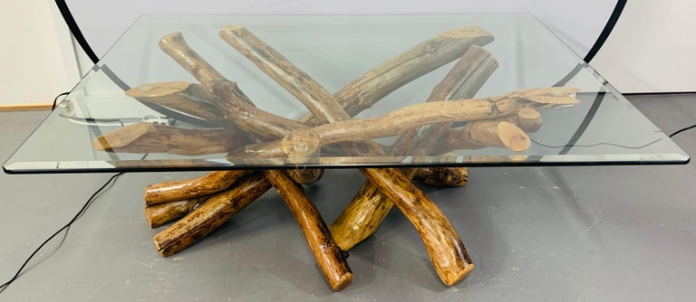 A rustic natural wood base coffee or cocktail table in an organic design fashion. This amazing table features veneered maple wood twist logs put together in an intertwining manner to present an artistic wood sculpture as the table base and a heavy