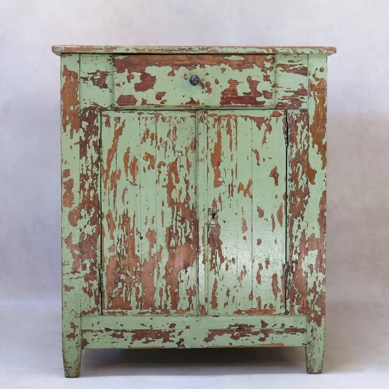 Charming pinewood cabinet, with peeling, glossy green paint. The two doors open onto shelving (rather deep). Small drawer beneath the top. Raised on short, slightly tapering feet.