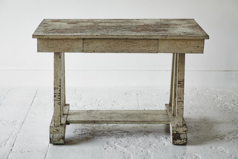 Rustic pale yellow painted desk with a stretcher base. The desk offers a single recessed drawer, original distressed paint adds to the rustic charm.