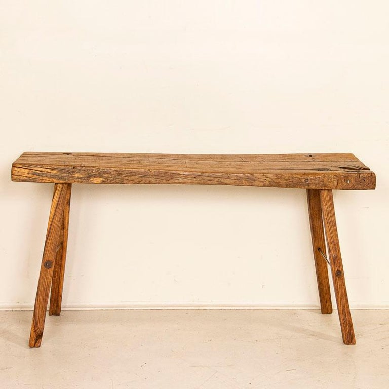 It is the knots, gnarls and old cracks that create the character in this rustic coffee table. The heft of the slab wood top draws one to it, but it is the deep gouges, marks, cracks and distress that make it so unique. Originally, this was likely a