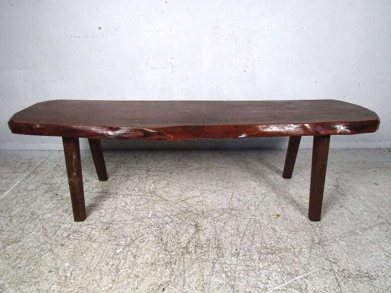 Rustic tree-slab coffee table. Live edge design, with a planned surface covered in a dark finish. Splayed legs support the table. An interesting addition to any interior. Please confirm item location with dealer (NJ or NY).