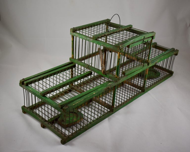 A charming rustic, handmade, vintage French Finch bird trapping cage, capable of catching two birds independently.   The bird lands on the trap to feed from the small food tray and it's weight causes the lid to drop down, trapping the bird inside.