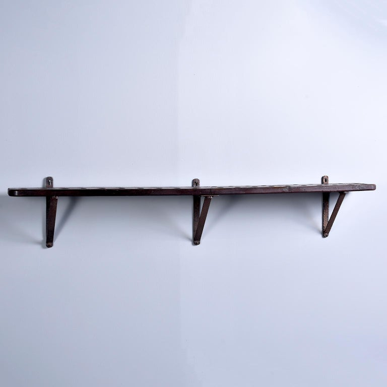 Early 20th century rustic French shelf-style wood and iron wine rack. Consists of heavy wood shelf with holes to store wine bottles upside down (keeps the cork wet) and iron supports. Great authentic piece for a home or commercial bar.