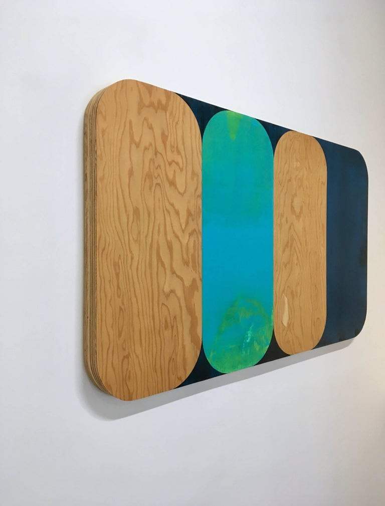 In this abstract acrylic painting on panel with round edges, soft geometric forms in vibrant bright turquoise and dark navy are offset by the natural wood grain of the light wood panel.  Hiller's paintings are the abstract interpretation of her